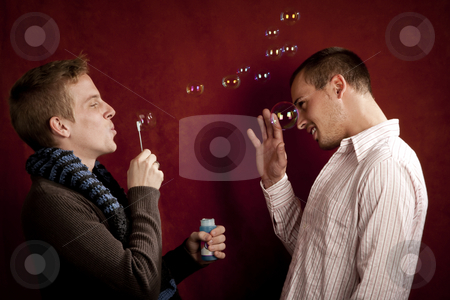 Young Man Blowing a Bubbles at Friend stock photo, Handsome young blonde man blowing a bubbles at friends by Scott Griessel