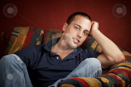 Handsome young man stock photo, Handsome young man reclining in a colorful chair by Scott Griessel