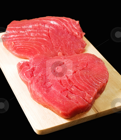Tuna steaks stock photo, Tuna steak on a wooden panel, isolated on a black background. by Sinisa Botas