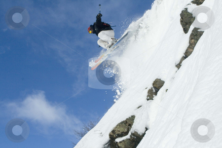 Snow skier jumping off a cliff stock photo, Back country snow skier jumping through powder by Audrey Amelie Rudolf