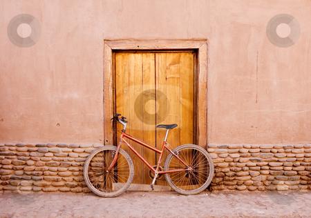 Desert bike stock photo, Bike sitting against the wooden door covered in dust by Audrey Amelie Rudolf