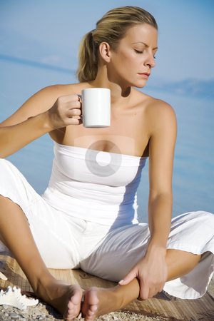 Healthy lifestyle stock photo, Young female drinking her morning herbal tea on the beach by Liv Friis-Larsen