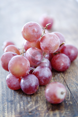 Red grapes stock photo, Fresh red grapes on rustic wood by Liv Friis-Larsen