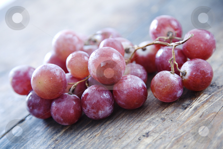Red grapes stock photo, Juicy fresh grapes on rustic wood by Liv Friis-Larsen