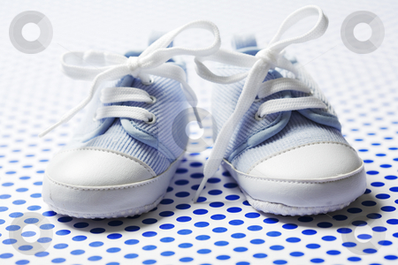 Boys baby shoes stock photo, Ltlle cute baby shoes on a blue pattern by Liv Friis-Larsen