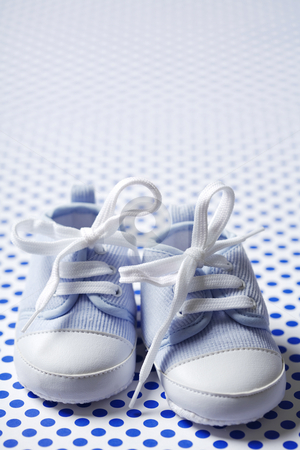 Boys shoes stock photo, Closeup of blue baby shoes on dotted background by Liv Friis-Larsen