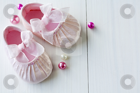 Baby shoes stock photo, Satin pink baby shoes on wooden floor, room for text, the floor-line is easily removed for a different cleaner look by Liv Friis-Larsen