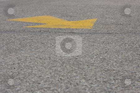 Yellow arrow on the ground stock photo, A yellow arrow painted on asphalt, with copy space below. by Kevin Woodrow