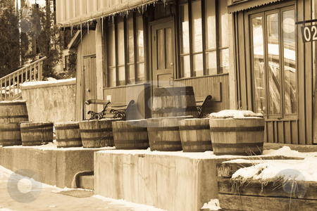 Old West Winter Scene stock photo, Wooden barrels outside of an old building, with a western feel to it. by Kevin Woodrow