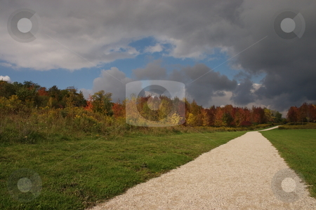 Pathway in the fall stock photo, Fall colors along a walking path, with a moody sky. by Kevin Woodrow