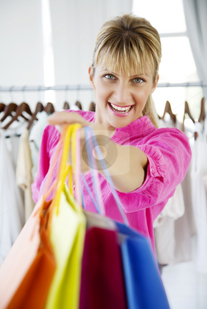 Shopping therapy stock photo, Young happy female in store with shopping bags by Liv Friis-Larsen