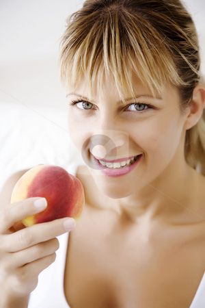 Eating peach stock photo, Happy female ating peach by Liv Friis-Larsen