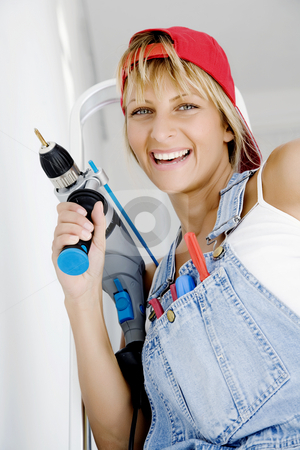 DIY woman stock photo, Woman in front of ladder with powertool and a range of tools in her pocket by Liv Friis-Larsen