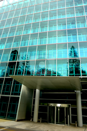 Front Door stock photo, The deserted front door of a large commercial office block, surrounded by trees reflected in the glass. One tree reflection appears to grow out of a pillar of the entrance. Also, contrast between light at top of building and dark inside door. by Alistair Scott