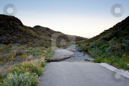 End of the road stock photo, Road ends abruptly into a dry water stream by Santiago Hernandez