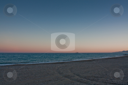 Cargo ship leaving at dusk stock photo, View of cargo ship.Mojacar at the other side of the bay by Santiago Hernandez