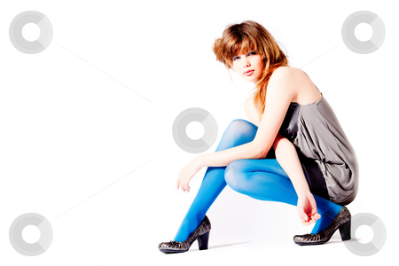 Teenager in blue pantyhose and grey blouse in a difficult pose stock photo, Studio portrait of a cute teenager by Frenk and Danielle Kaufmann
