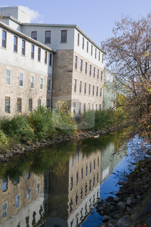 Factory reflection along the river stock photo, An old factory building, lining a small river, with its reflection visible in the still water. by Kevin Woodrow