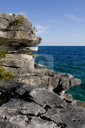 Natures stepping stones stock photo, Focus on rock formations in the foreground, and deep blue water of Georgian Bay in the background. by Kevin Woodrow