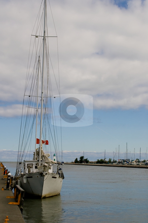 Lonely Sailboat stock photo, A lone docked sailboat, an empty canal behind.  A blue sky mid-image with cloud covering the top of the image. by Kevin Woodrow
