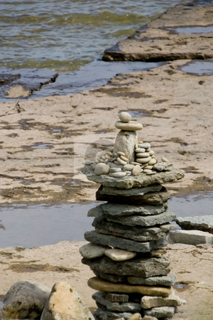 Build-up of stones stock photo, A statue of stones at the water's edge. by Kevin Woodrow