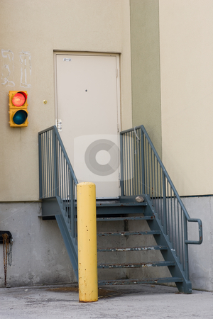 Loading dock stairs and stoplight stock photo, Loading dock stairs, door and a red light signaling trucks can not unload. by Kevin Woodrow
