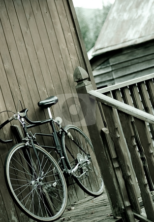 Bicycle at rest stock photo, A bicycle resting up against the side of a house. by Kevin Woodrow