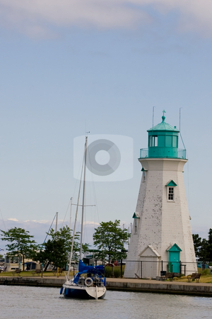 Sailing past a lighthouse stock photo, A sailboat passes a white and green colored lighthouse as it heads up the canal to open water. by Kevin Woodrow