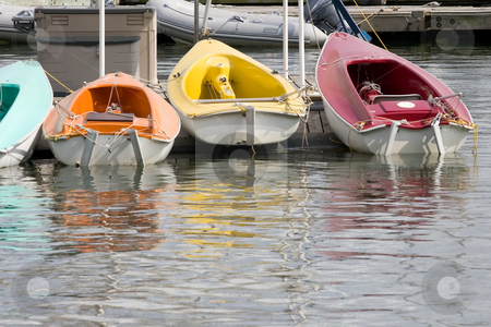 Colorful Boats stock photo, A line of small colorful boats in the water at a marina. by Kevin Woodrow