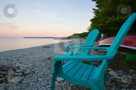 Cottage Life stock photo, Focus on two blueish green chairs on a rocky beach, overlooking the bay, as the sun sets. by Kevin Woodrow