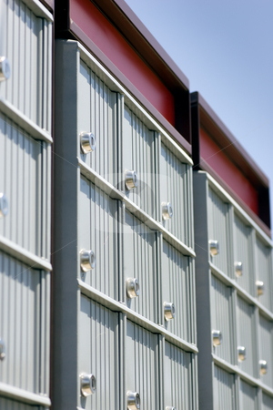 Checking the mail stock photo, Looking up at a set of mailboxes, focus on the locks, with blue sky in the background. by Kevin Woodrow