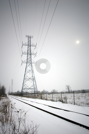 Hydro lines along train tracks in winter stock photo, Focus on a large hydro tower which runs along railroad tracks in winter, snow covering the ground, with the sun visible in the haze. by Kevin Woodrow