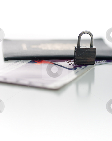 Travel Security stock photo, Picture of a Canadian Passport, a credit card, and a plan ticket, with focus on a small padlock, isolated on white. by Kevin Woodrow