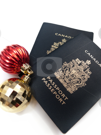 Ornaments and Passports stock photo, Two christmas baubles beside two Canadian passports, isolated on white. by Kevin Woodrow