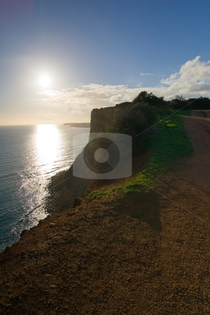 Lagos Cliffs at sunset stock photo, The cliffs of Lagos, Portugal, as the sun sets, shot into the sun. by Kevin Woodrow