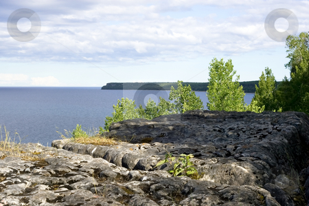 Georgian Bay lookout stock photo, Porous rock and some foliage in the foreground, with Georgian Bay in the background. by Kevin Woodrow