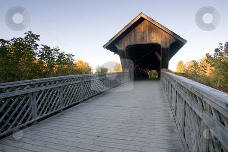 Covered Walking Bridge, Wideangle stock photo, A wide angle view of a covered walking bridge, located in Guelph, Ontario, Canada, with a blue sky background and surrounding fall colors. by Kevin Woodrow