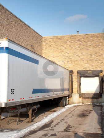 Loading dock stock photo, A loading dock with one empty bay and a trailer in the other bay. by Kevin Woodrow