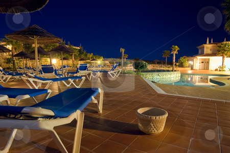 Evening Around Resort Pool stock photo, A late night shot of a deserted resort pool, with lounging chairs, and umbrellas. by Kevin Woodrow