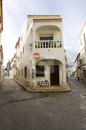 Fork in the road stock photo, A narrow old Portuguese town street, with grafiti on the center building. by Kevin Woodrow