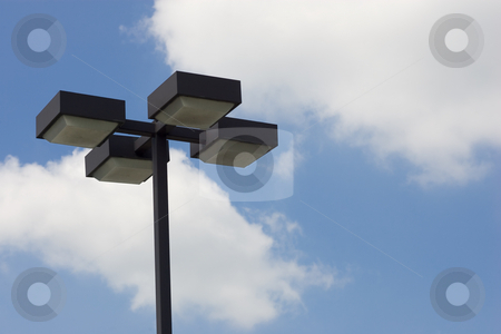 Lampost on sky stock photo, A 4-light lamp post against a blue sky and clouds. by Kevin Woodrow