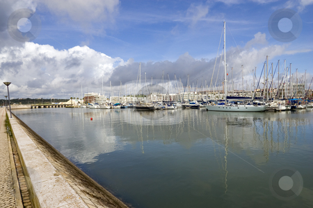 Marina in the clouds stock photo, View of the marina with the reflection of clouds in the still water.  Shot in Lagos, Portugal. by Kevin Woodrow