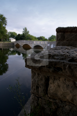 Stone wall with bridge background stock photo, An old rock wall on the edge of the speed river, with a bridge in the background.  Guelph, Ontario, Canada by Kevin Woodrow