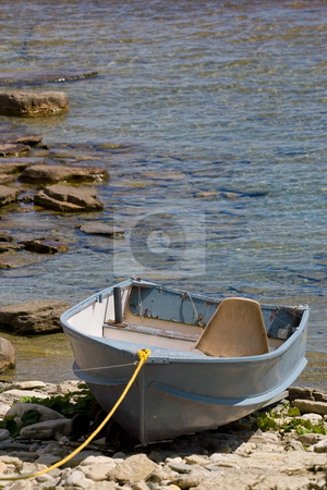 Washed up on shore stock photo, An old boat, tied up on the rocks, at the waters edge. by Kevin Woodrow