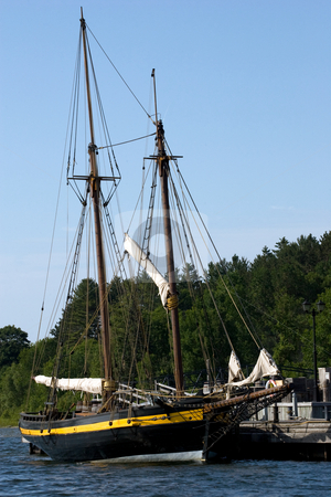 Old Pirate / Sailing ship stock photo, An old Vintage sailing ship, docked, blue sky in the background. by Kevin Woodrow
