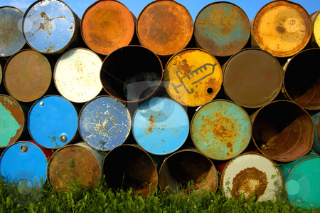 Barrels on end stock photo, A stack of old oil drums at a music festival, ready to be set out as rubbish bins. One of them is for used syringes. Blue sky above and behind, green grass below. by Alistair Scott