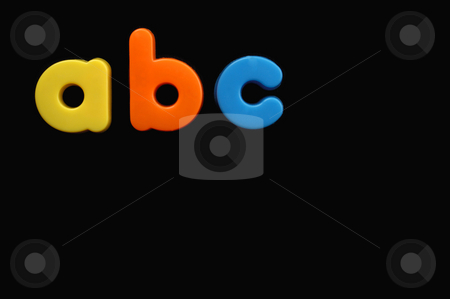 Child's letters stock photo, The letters a, b and c from a child's toy alphabet set, placed on a black background. Space for text elsewhere in the image. by Alistair Scott