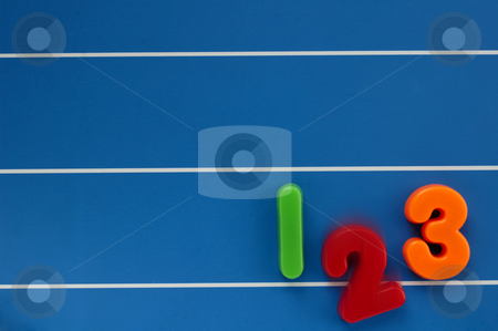 Drop-out stock photo, The numbers 1, 2 and 3 from a child's toy learning set, on a blue, lined background. The number 2 dropping out of the line, with motion blur. by Alistair Scott