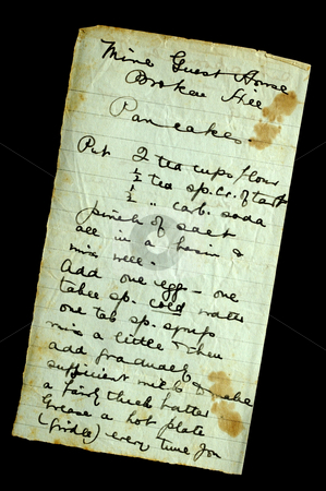 Pancake recipe stock photo, A hand-written recipe for pancakes, on stained and crumpled paper, isolated on black. Found in a 100-year old cookery book. by Alistair Scott