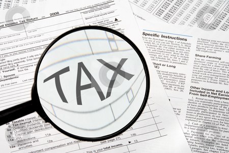 Taxes stock photo, Federal tax forms under a magnifying glass. by Robert Byron